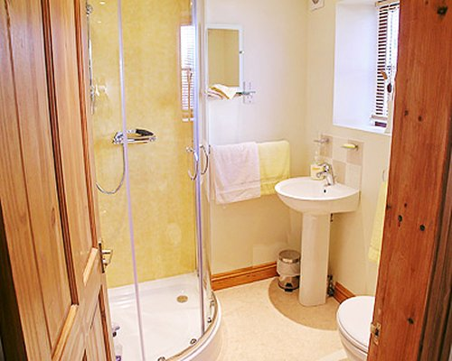 A bathroom with a standing shower stall and single sink.