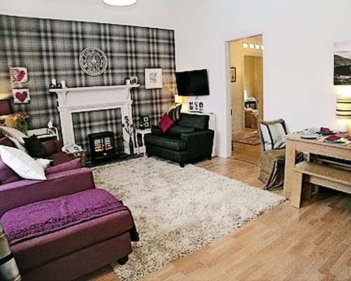 A well furnished living and dining area with a television and fireplace.