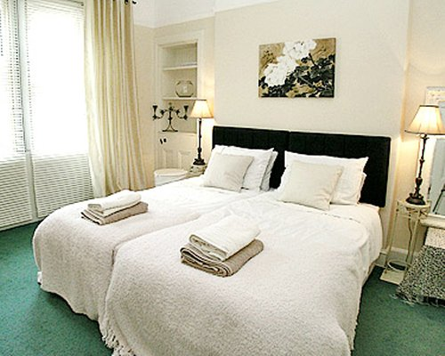 A well furnished bedroom with twin beds and an outside view.