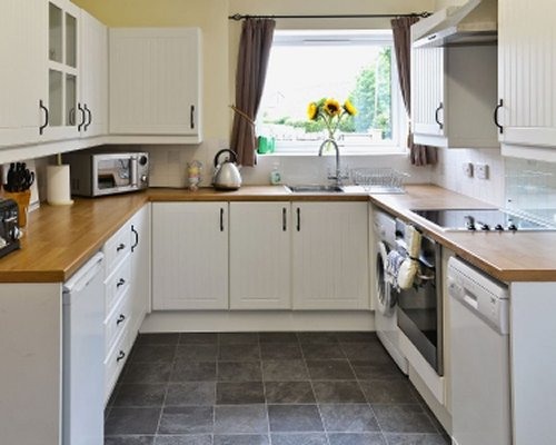 A well equipped kitchen with a microwave and an outside view.