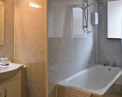 A bathroom with a closed sink vanity bathtub and shower.