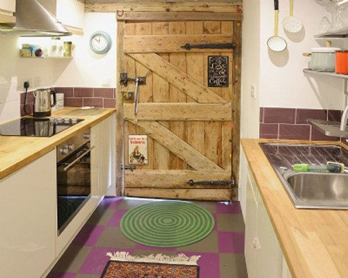 A view of well equipped kitchen and entrance door.