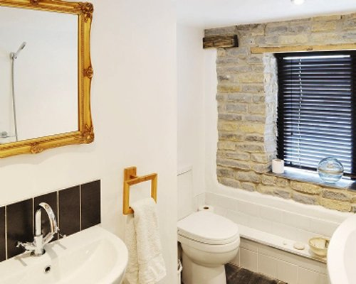 A bathroom with a sink vanity and a window within a stone wall.