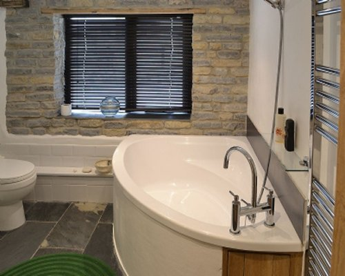 A bathroom with a corner bathtub next to a stone wall and a wall towel heater.