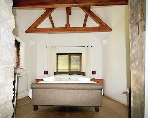 A bedroom with a large bed and window with exposed wooden rafters.