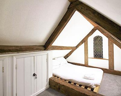 An upstairs bedroom with a bed and exposed wooden rafters.