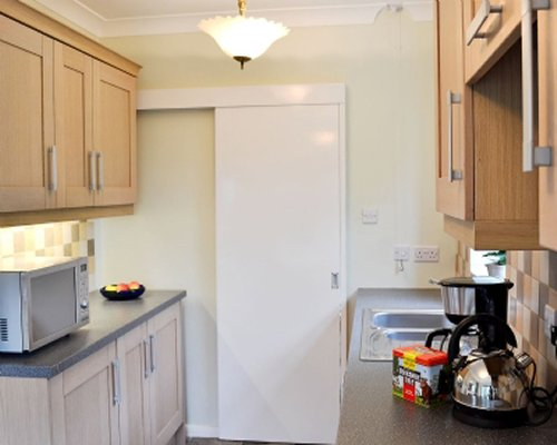 A well equipped kitchen with a sliding door.