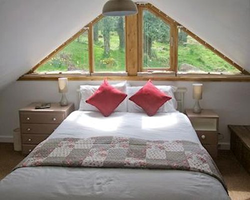 An upstairs bedroom with a triangular window above a large bed at the roof peak.