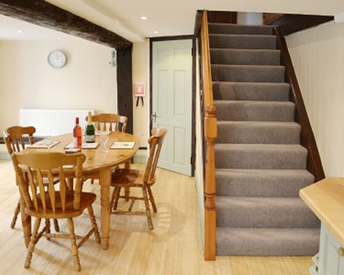 A well furnished dining area alongside a staircase.