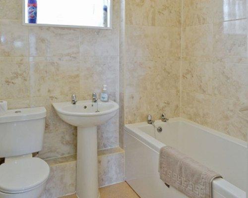 A bathroom with shower bathtub and a single sink.