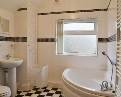 A bathroom with a corner bathtub and a wall towel heater.