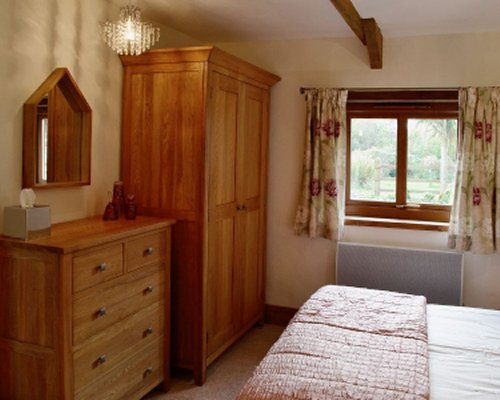 A well furnished bedroom with a wardrobe and an outside view.