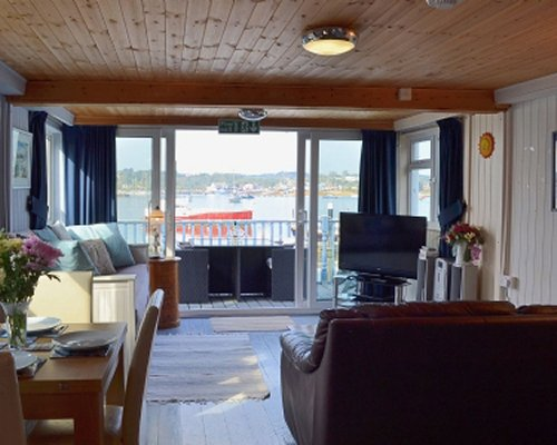 A well furnished living and dining area with a television and the beach view.