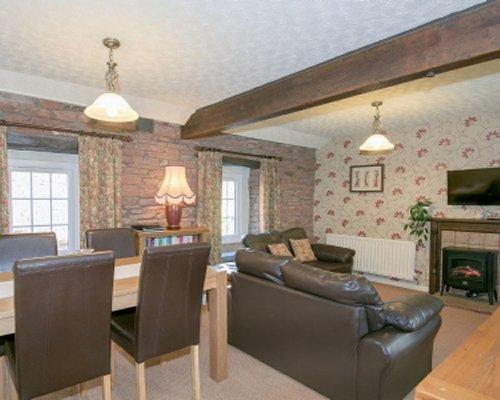 A well furnished living and dining area with a television fire in the fireplace and an outside view.