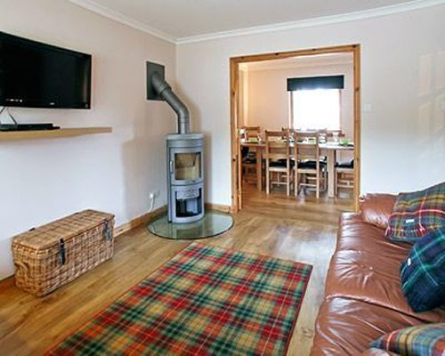 A well furnished living room with a television gas log fireplace and dining area.