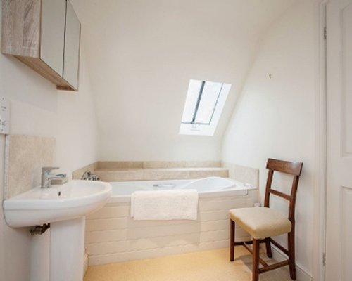 A bathroom with a bathtub shower and sink.