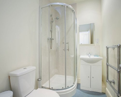 A bathroom with a closed sink and shower stall.