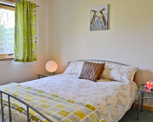 A well furnished bedroom with a lamp and an outside view.