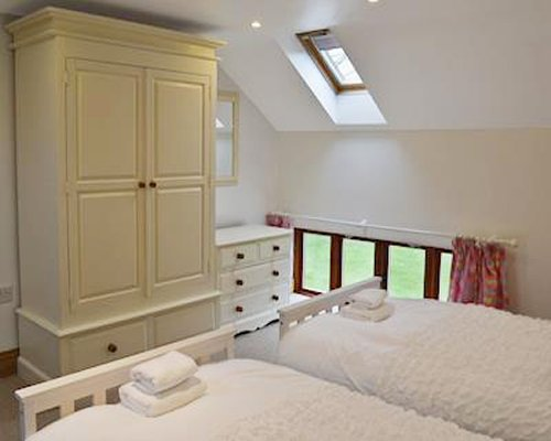 A furnished bedroom with twin beds windows and a skylight.