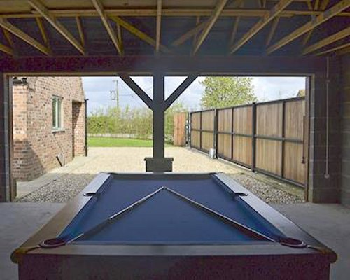 A pool table with a view outside.