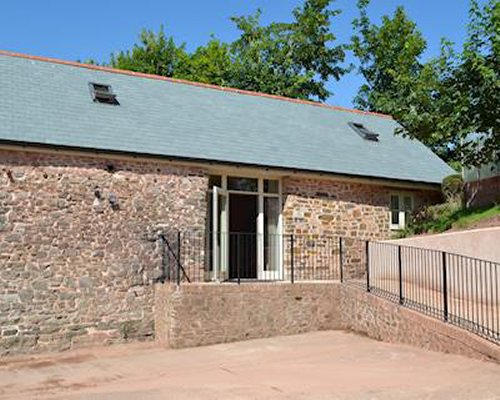 An exterior view of stone cottage with a wall and fence.