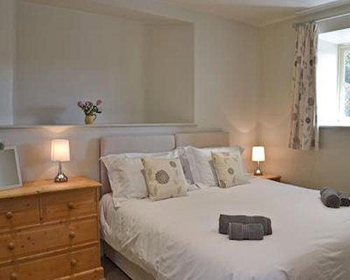 A furnished bedroom with a large bed and window.