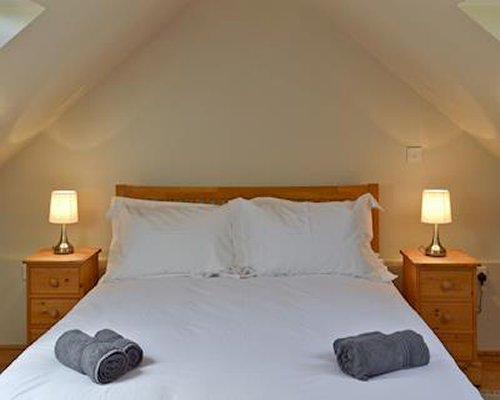 A bedroom with a large bed and skylights.