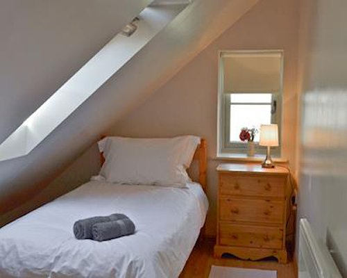A bedroom with a twin bed and a skylight.