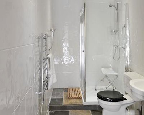 A bathroom with a shower stall a wall towel heater.