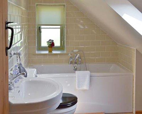 A bathroom with a sink bathtub and a window.