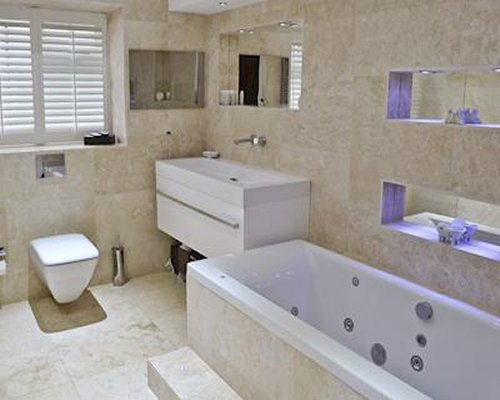A bathroom with shower bathtub and single sink vanity.