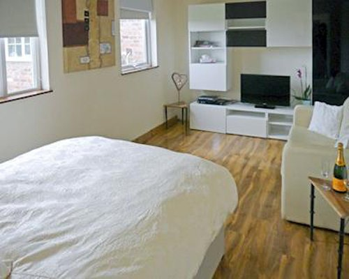 A well furnished bedroom with a television living area and outside view.