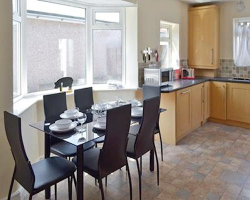 A well equipped kitchen with a dining table and a large window.