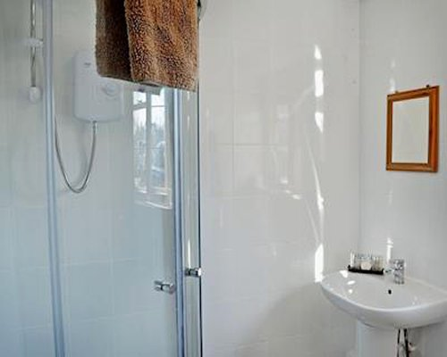 A bathroom with a shower stall and a pedestal sink.