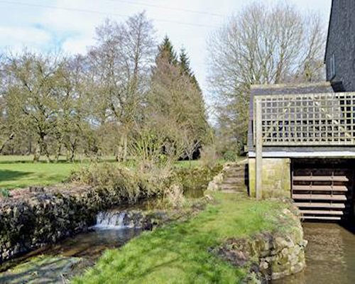 Yard view with stone exterior next to water with mill wheel.