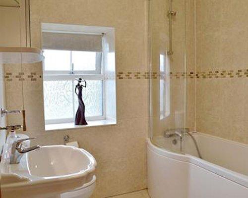 A bathroom with bathtub shower and single sink.