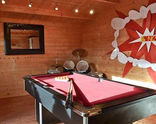 An indoor recreational area with a pool table and drums.