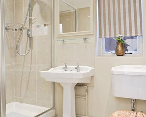 A bathroom with single sink vanity and shower.