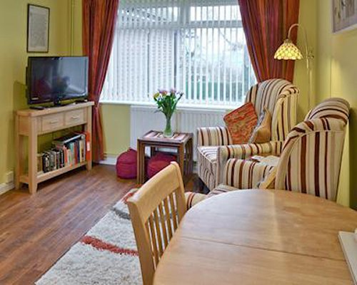 A well furnished living room with a television bookshelf dining area and outside view.