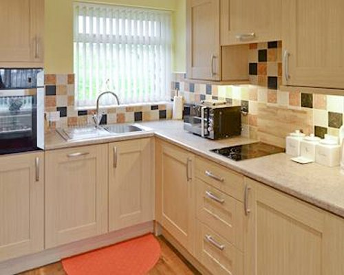 A well equipped kitchen with the microwave oven and stove.