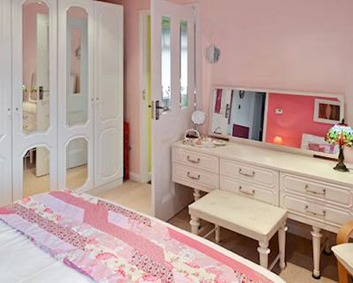 A well furnished bedroom with a dresser.