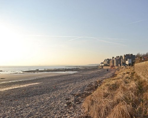 View of the beach and sea alongside Cardy Cottage at dusk.