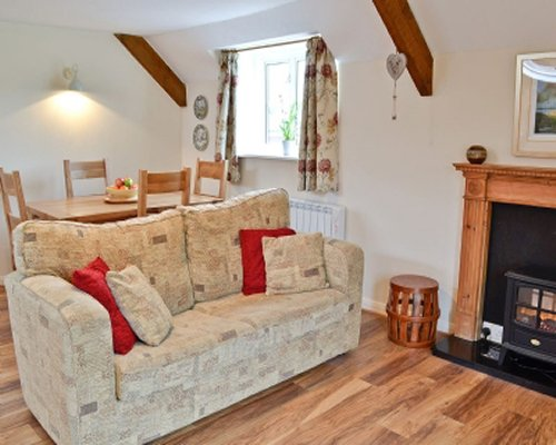 A well furnished living and dining area with a fire in the fireplace and an outside view.