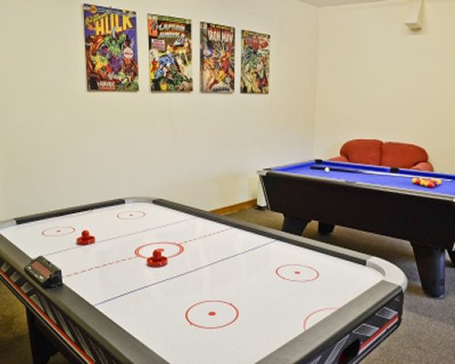 Indoor recreation room with pool table and air hockey.