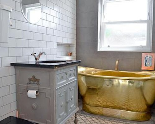 A bathroom with single sink vanity and a gold bathtub.