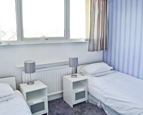 A well furnished bedroom with two twin beds and lamps.