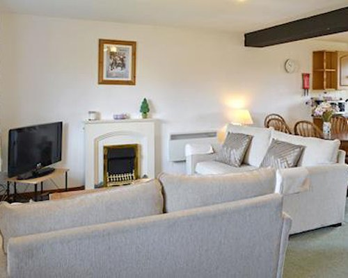 A furnished living room with dining area and television.