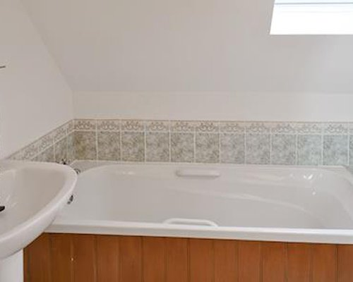 A bathroom with bathtub and a single sink vanity.