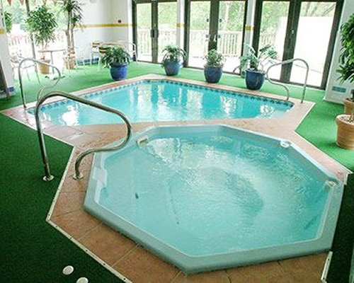Indoor swimming pool and hot tub with outside view.