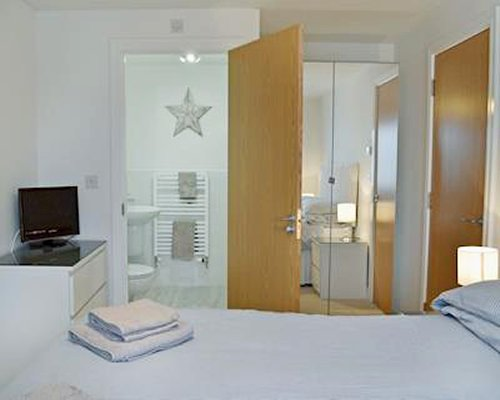 A well furnished bedroom with a television and bathroom.